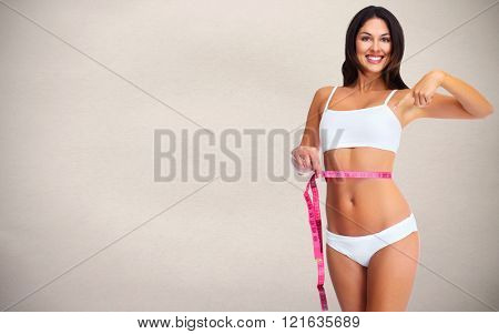 Woman with measuring tape over gray background.