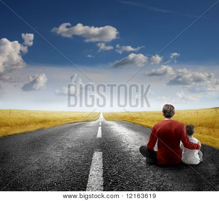 Father and son sitting on a road
