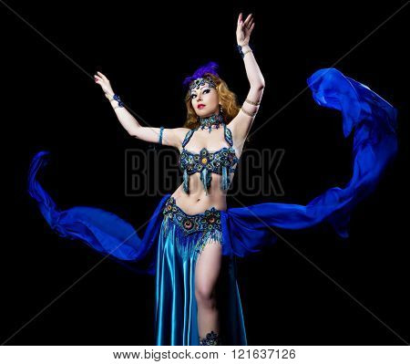 beautiful belly-dancer with long ginger hair and arabic makeup, isolated against  blue studio background