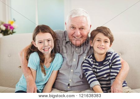 Portrait of grandfather and grandchildren sitting together on sofa in living room