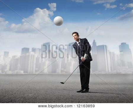 Businessman playing golf with cityscape on the background