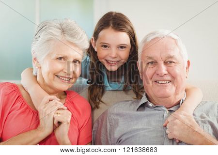 Portrait of smiling granddaughter embracing her grandparents in living room