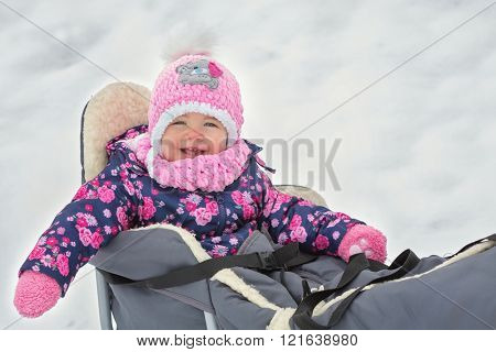 Cute little girl sitting on her sledge in winter day