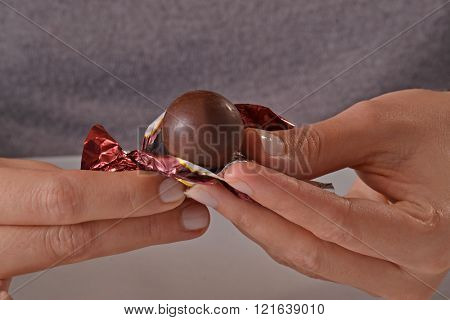 Opening chocolate candy ball from bag.