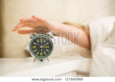 Pretty woman shutting off her alarm clock in the bedroom
