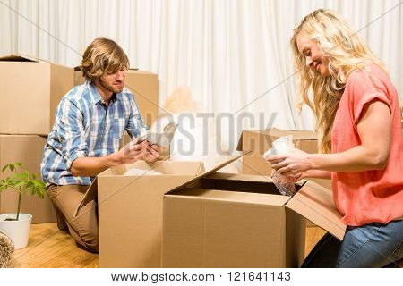 Happy couple unpacking after move in their new house