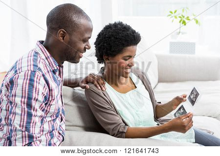 Pregnant couple sitting on sofa and looking at ultrasound scan at home