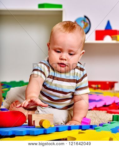 Kid baby boy lying on floor and plying with puzzle toy.  Early baby development.