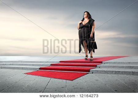 Fat elegant woman standing on a red carpet