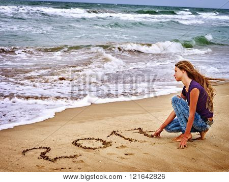 Summer girl sea.  Girl is writting in sand  2017 near ocean with waves. Sea concept.