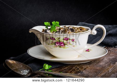 Mushroom sauce with parsley in a sauceboat on wooden table