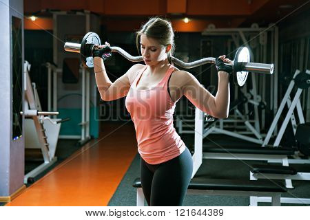 Portrait Of Serious Athlete Girl Holds Metal Barbell