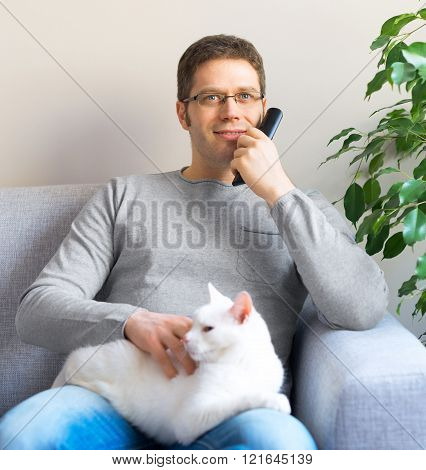 Man relaxing on the sofa with tv remote control. Watching TV with his cat.