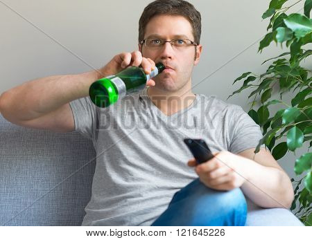 Man watching TV with bottle of beer.
