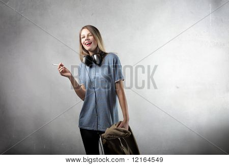 Smiling beautiful woman with headphones smoking a cigarette