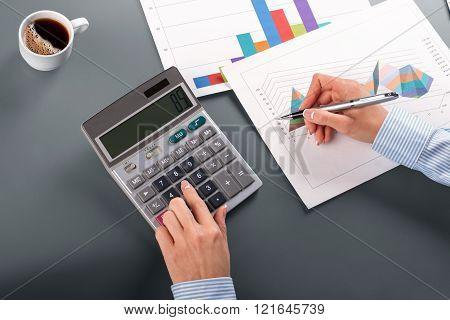 Close-up of businesswoman using calculator.