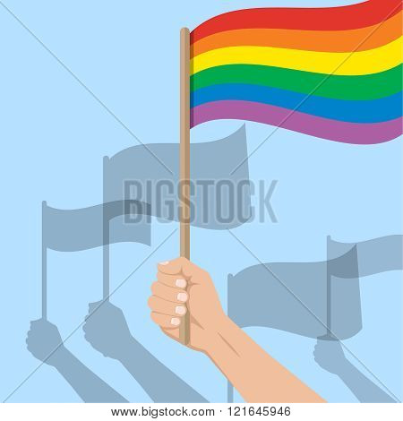 The hands of people flying flags. The hand in the foreground flying an iridescent flag.