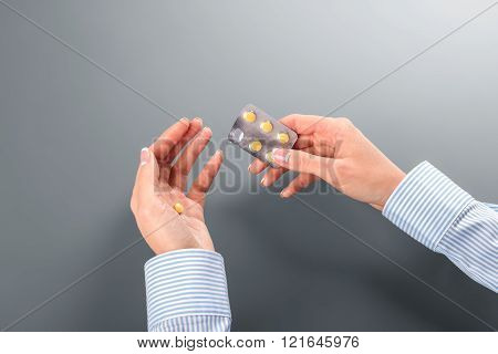Female taking pill from blister.