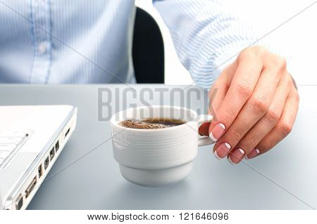 Lady's hand holding coffee cup.