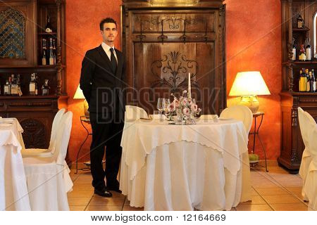 Young waiter standing beside a table in a luxury restaurant