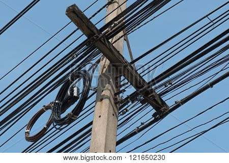 Messy power lines on electric pole with clear sky