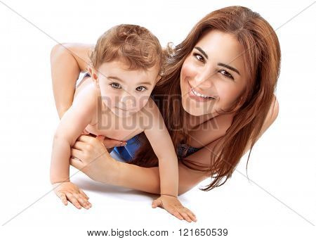 Portrait of happy joyful mother playing with her adorable son, lying down in the studio over white background, enjoying motherhood