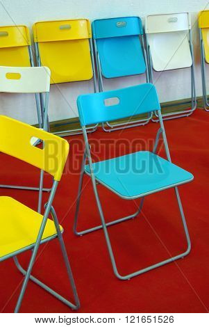 Colorful chairs on red carpet and white wall