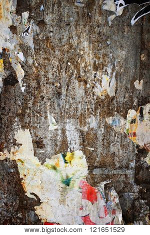 Background of messy wall surface with remains old ripped posters