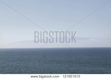 small sailing boat on atlantic ocean between tenerife and la gomera on blue sea under blue sky