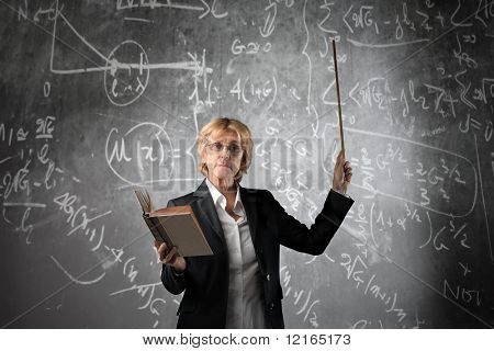 Teacher in a classroom holding a book