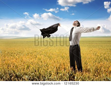 Happy businessman standing on a wheat field