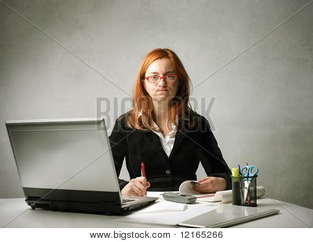 Stressed businesswoman working at her desk in front of a laptop