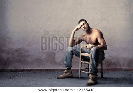 Beautiful brawny man sitting on a chair