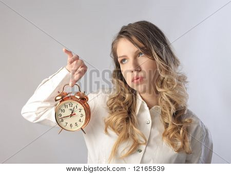 Sad young woman holding an alarm clock