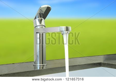 Water flow faucet granite counter on green environment.