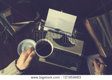 Hipster man with coffee writing on old typewriter.