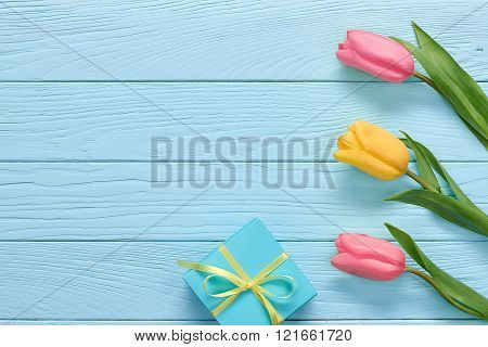 Mothers Day background. Tulips, gift box on wood