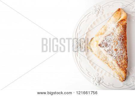 Cream puff with powdered sugar on the white plate top view