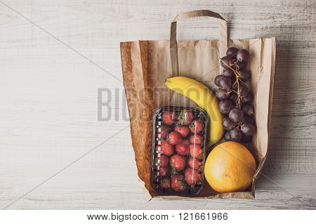 Strawberry with different fruit inside a paper bag horizontal