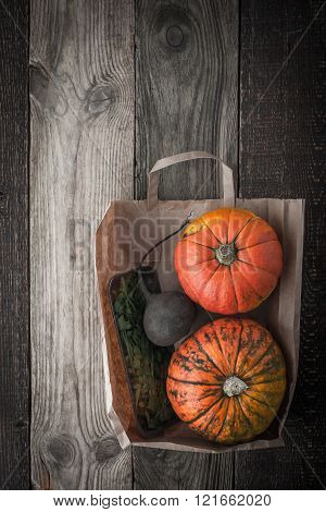 Pumpkins turnip and greens inside a paper bag