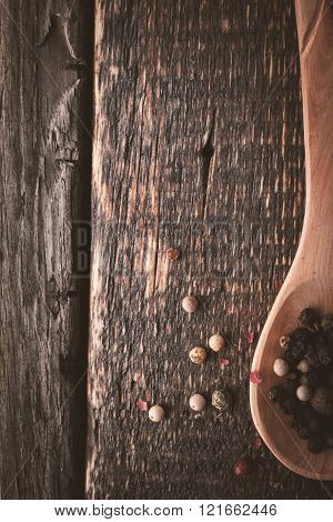 Wooden spoon with pepper mix on the wooden background vertical