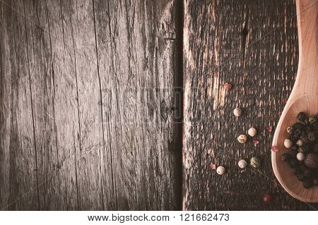 Wooden spoon with pepper mix on the wooden background horizontal