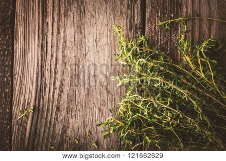 Bunch of thyme on the old wooden board top view