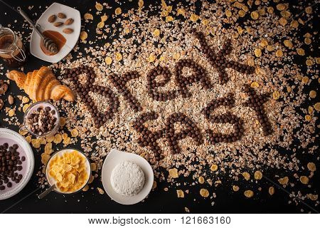 Breakfast word made by chocolate crispy ball on the muesli background with breakfast attributes
