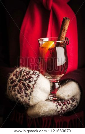 Mulled whine in the hands in knitted mittens vertical