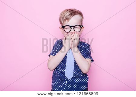 Little adorable kid in tie and glasses. School. Preschool. Fashion. Studio portrait over pink