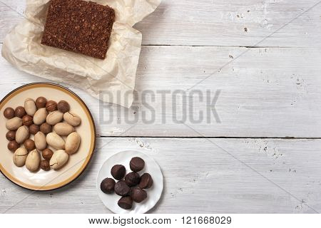 Nuts truffle candy and chocolate cake on the white wooden table horizontal