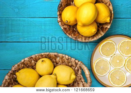 Yellow colorful lemons in a basket and slices on a plate on the bright cyan wooden table horizontal