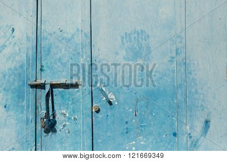 dusty blue metal door with slide bolt and hand prints in Merzouga, Morocco