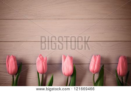 Mothers Day background. Tulips pink on wood